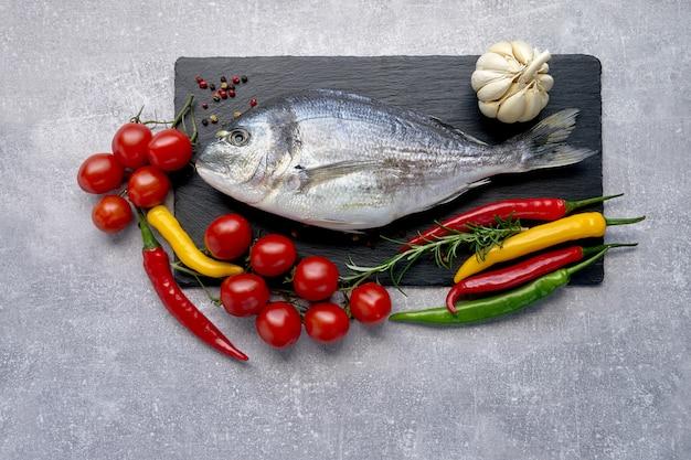 Raw dorada fish on black slate cutting board with vegetables around