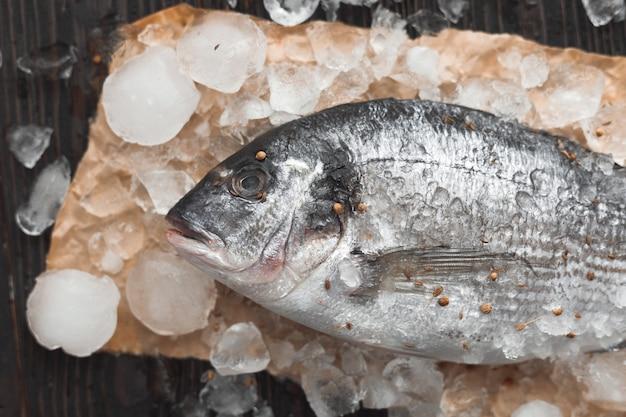 生のドラダ魚またはヨーロッパヘダイ、レモンスライス、ローズマリー、黒い木製の背景、フラットレイ、上面図