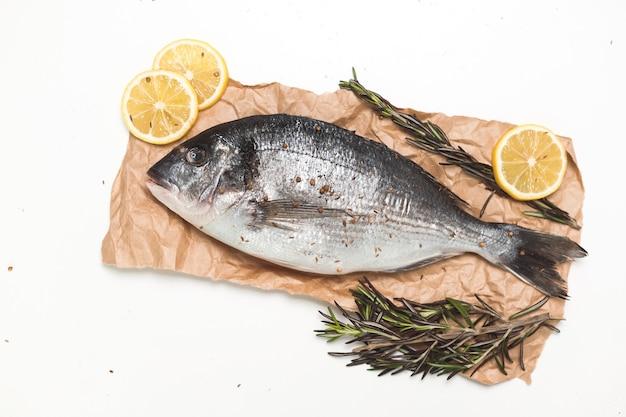 白い背景、フラットレイ、上面図の上の紙に生のドラダ魚またはヨーロッパヘダイ
