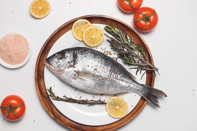 生のドラダ魚またはヨーロッパヘダイは、白い背景、フラットレイ、上面図の白いプレートで提供されます