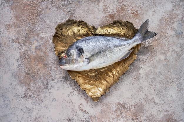 Raw dorado fish on the heart shaped dish. sea bream or dorado fish. top view, copyspace