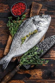 Сырая рыба дорадо на разделочной доске с ножом. темный деревянный фон. вид сверху.