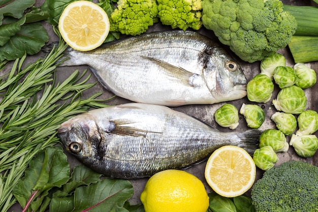 Сырая рыба дорадо на решетке металлического гриля с зелеными овощами и зеленью.