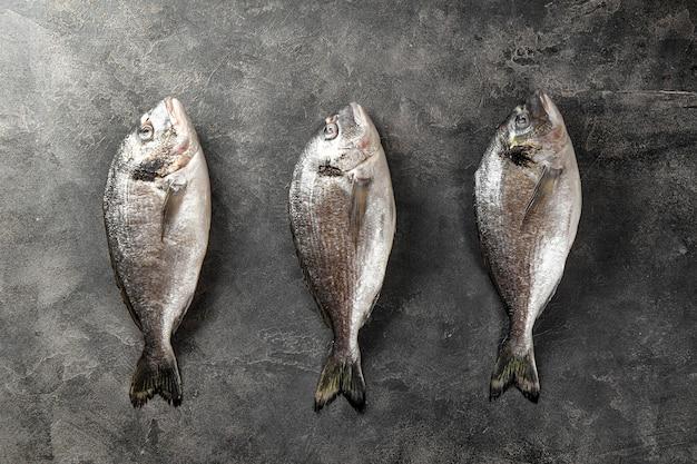 Сырая рыба дорадо на темно-сером фоне, вид сверху, минималистичный фон с морепродуктами