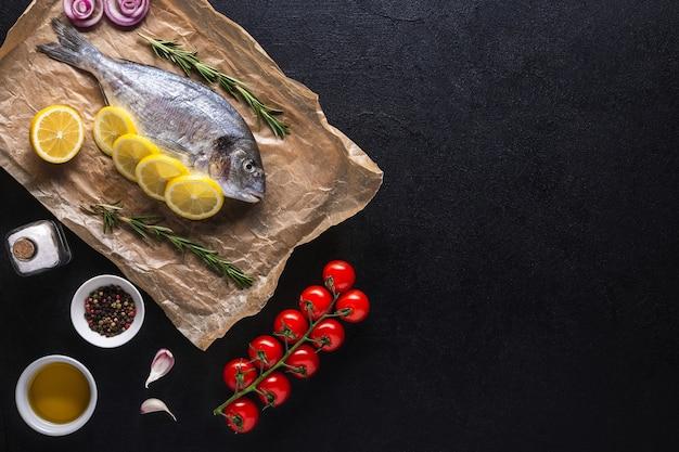 Сырая рыба дорадо, приготовленная для приготовления с кусочками лимона, розмарина, лука, помидоров черри, специй и масла на черном фоне. вид сверху. скопируйте пространство.