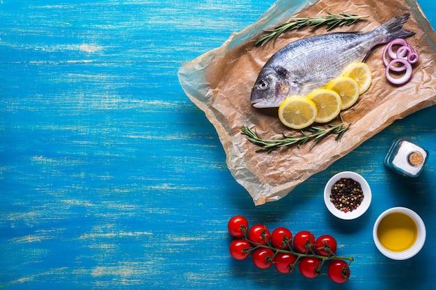 Сырая рыба дорадо, приготовленная для приготовления с кусочками лимона, розмарина, лука, помидоров черри, специй и масла на синем фоне. вид сверху. скопируйте пространство.