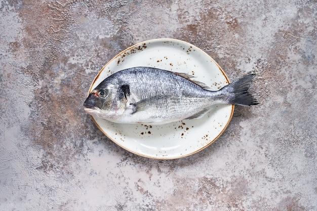 Raw dorado fish on the white dish. sea bream or dorada fish. top view, copyspace