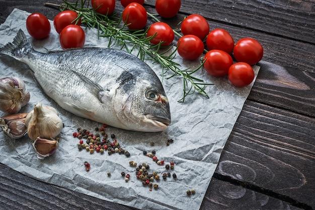 素朴なテーブルにニンニクとトマトを添えた生のドラドフィッシュ。鯛またはドラダ魚。上面図
