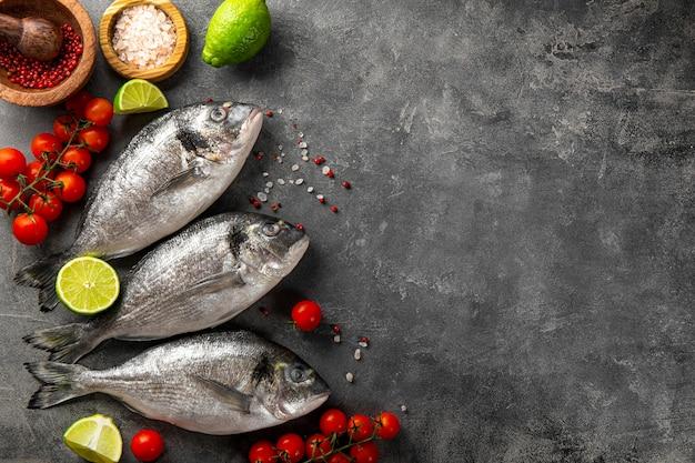 Сырая рыба дорадо с лаймом и специями для приготовления на сером фоне, вид сверху, копировальное пространство для текста