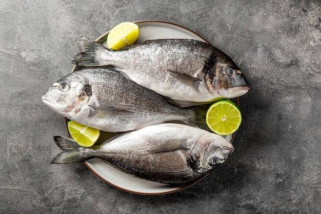 Сырая рыба дорадо с лаймом на тарелке и на темно-сером фоне, вид сверху минималистичный