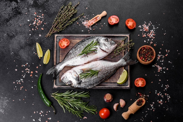 まな板で調理するスパイスと生のドラド魚。新鮮な魚のドラド。ドラドとテーブルで調理するための材料