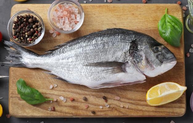 Сырая рыба дорадо со специями, приготовленная на разделочной доске