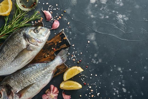 검은 슬레이트, 돌 또는 콘크리트 배경에 레몬, 백리향, 마늘, 체리 토마토, 소금을 만들기 위한 재료를 넣은 생도라도 신선한 생선이나 도미. 복사 공간이 있는 상위 뷰입니다.
