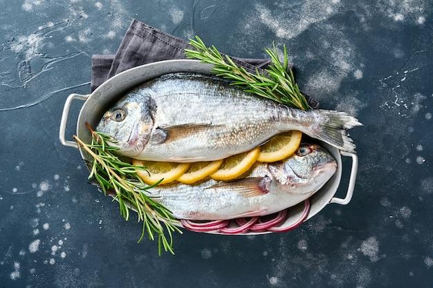 Сырая свежая рыба дорадо или морской лещ с ингредиентами для приготовления лимона, тимьяна, чеснока, помидоров черри и соли на черном сланце, камне или бетонном фоне. вид сверху с копией пространства.