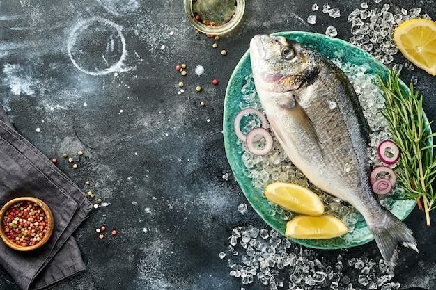 Сырая свежая рыба дорадо или морской лещ с ингредиентами для приготовления лимона, тимьяна, чеснока, помидоров черри и соли на льду на черном сланце, камне или бетоне. вид сверху с копией пространства.