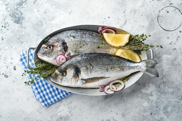 밝은 회색 슬레이트, 돌 또는 콘크리트 배경에 레몬, 백리향, 마늘, 체리 토마토, 소금을 만들기 위한 재료를 넣은 생 도라도 신선한 생선이나 도미. 복사 공간이 있는 상위 뷰입니다.
