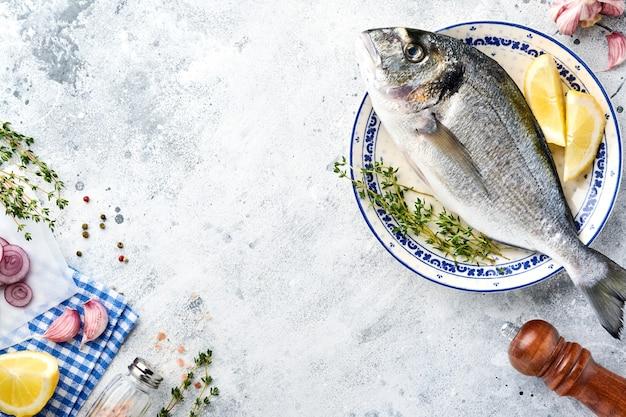 Сырая свежая рыба дорадо или морской лещ с ингредиентами для приготовления лимона, тимьяна, чеснока, помидоров черри и соли на светло-сером фоне из сланца, камня или бетона. вид сверху с копией пространства.