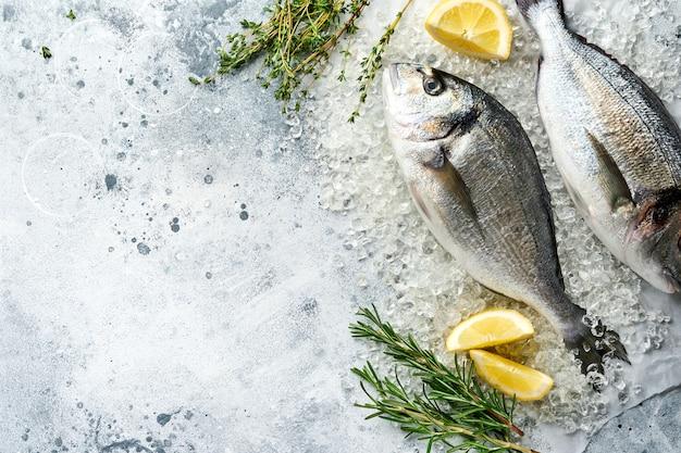 연한 회색 슬레이트, 돌 또는 콘크리트 배경에 레몬, 백리향, 마늘, 체리 토마토 및 소금을 만들기위한 재료가 들어있는 생도라도 신선한 생선 또는 도미. 복사 공간이있는 상위 뷰.