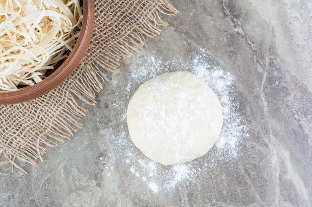 石の上に生の生地と粉チーズ。