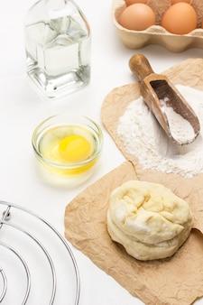 生の生地と小麦粉を紙にすくい取ります。ボウルに卵黄、ボトルに水。白色の背景。上面図 Premium写真