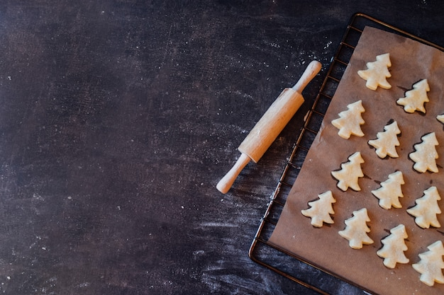 Raw dough cookies in christmas tree shape ready to bake