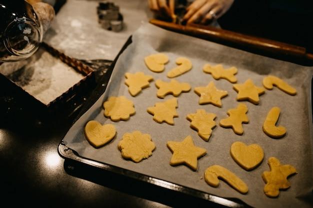 トレイにベーキングペーパー上のさまざまな形の生の生地のクッキー