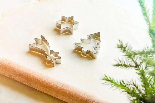 Сырое тесто для рождественского печенья и формочки для печенья. скалка, формы и ветки ели.