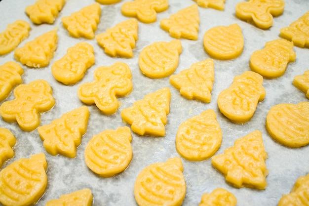 Raw dough gingerbread christmas cookies for childrenin form of ball, fir tree, snowman