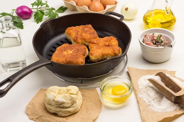 Бумага, сырое тесто. жареные пироги с мясом на сковороде. голова лука и желток в миске. белый фон. вид сверху