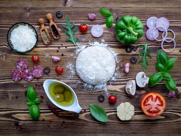Raw dough with ingredients for homemade pizza on shabby wooden background.