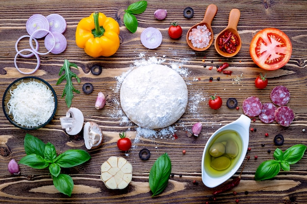 Raw dough with ingredients for homemade pizza
