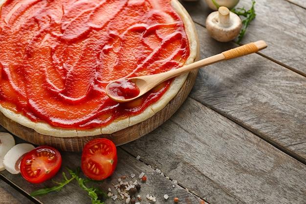 トマトソースとテーブルの上のピザの材料と生の生地