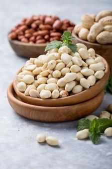 Сырые сушеные свежие арахисовые орехи на каменном фоне