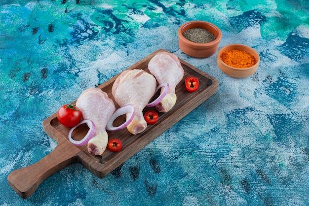 Bacchette e verdure crude su una tavola, sui precedenti blu.