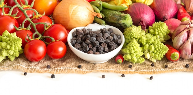 Raw dry black chickpea and vegetables isolated on white close up
