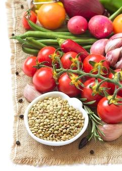 ボウルに生の乾燥緑レンズ豆と黄麻布の野菜を白の分離をクローズアップ