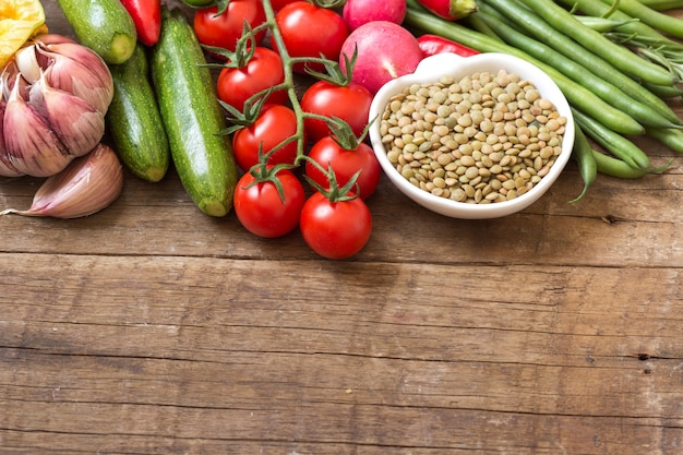 ボウルに生の乾燥グリーンレンズ豆と木製のテーブルで野菜をコピースペースでクローズアップ