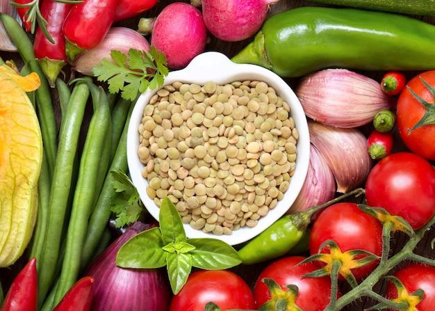 生野菜トップビューの間のボウルに生乾燥グリーンレンズ豆