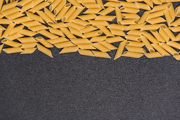 Raw dry italian pasta on grey background