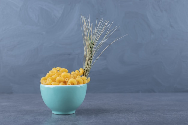 Raw dry macaroni in blue bowl with wheat.