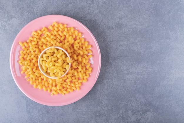 Maccheroni asciutti crudi sul piatto rosa.