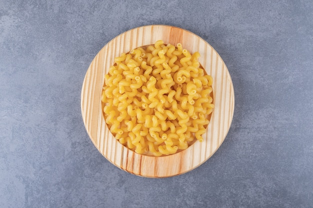 Raw dry macaroni on wooden plate.