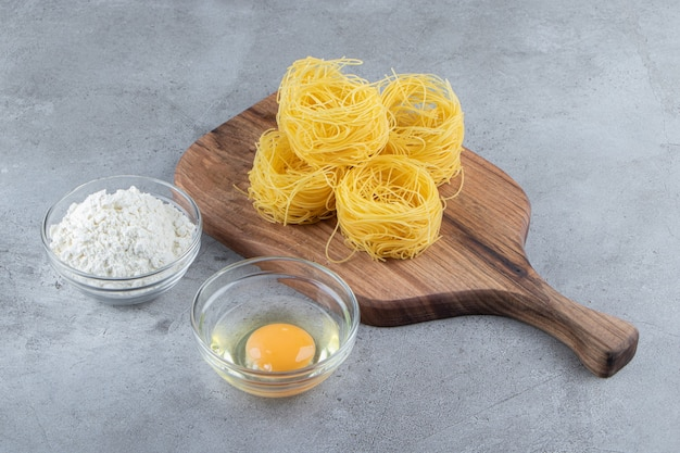 Raw dry nest pasta with raw egg and a glass bowl of flour on a stone surface .