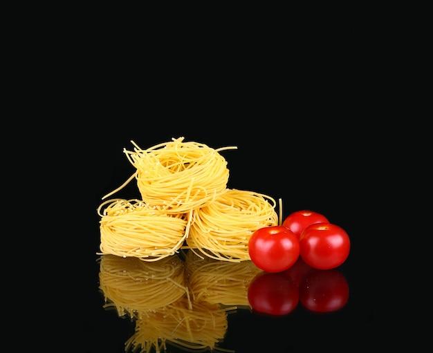 トマトと黒の反射と生のドライネストパスタ