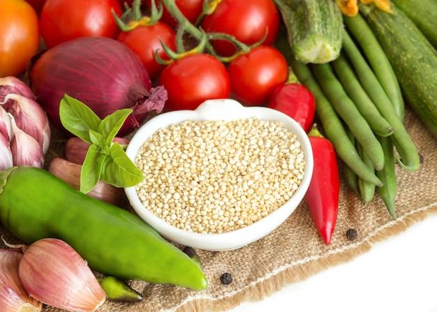 ボウルと黄麻布の野菜の生の乾燥キノアは白の分離をクローズアップ