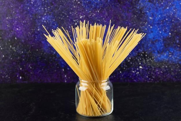 Сырые сухие спагетти в стеклянной банке на ярком столе.