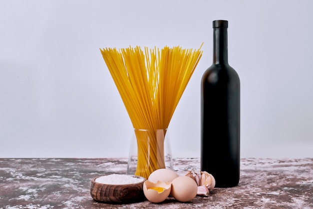 Raw dry spaghetti with flour and eggs on wooden table.