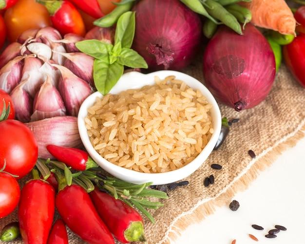 黄麻布の野菜とボウルに生の乾燥全体の白米のクローズアップを分離します。