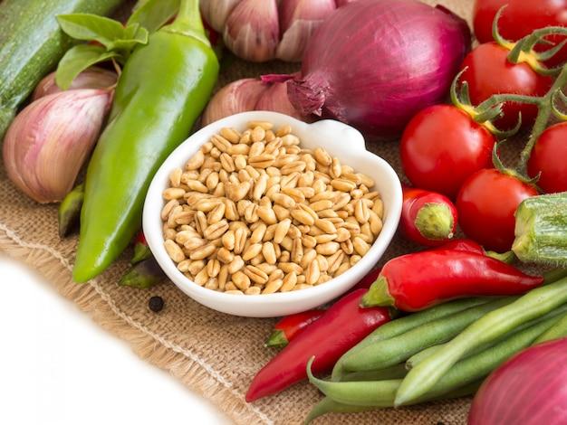 ボウルに生乾燥全粒小麦と黄麻布の野菜を白の分離をクローズアップ