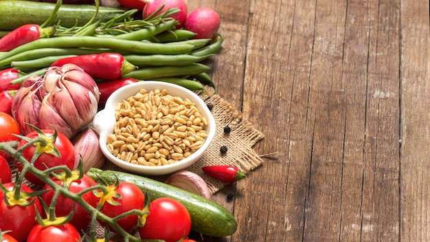 ボウルに生の乾燥全粒小麦と木製のテーブルで野菜をコピースペースでクローズアップ
